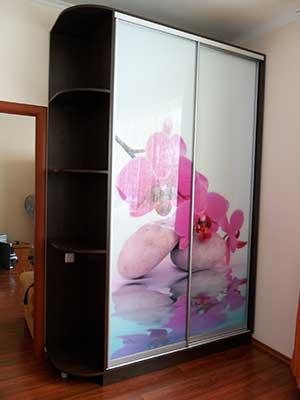 Светлый рисунок фотопечати под стеклом удачно контрастирует с корпусом шкафа цвета венге.