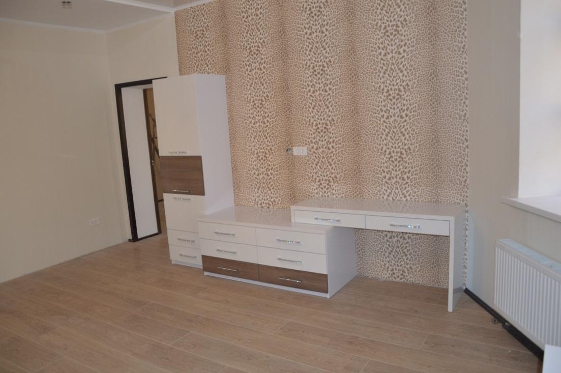 14. Лаконичный комплект мебели с глянцевыми белыми фасадами, дополненными «древесным» декором.